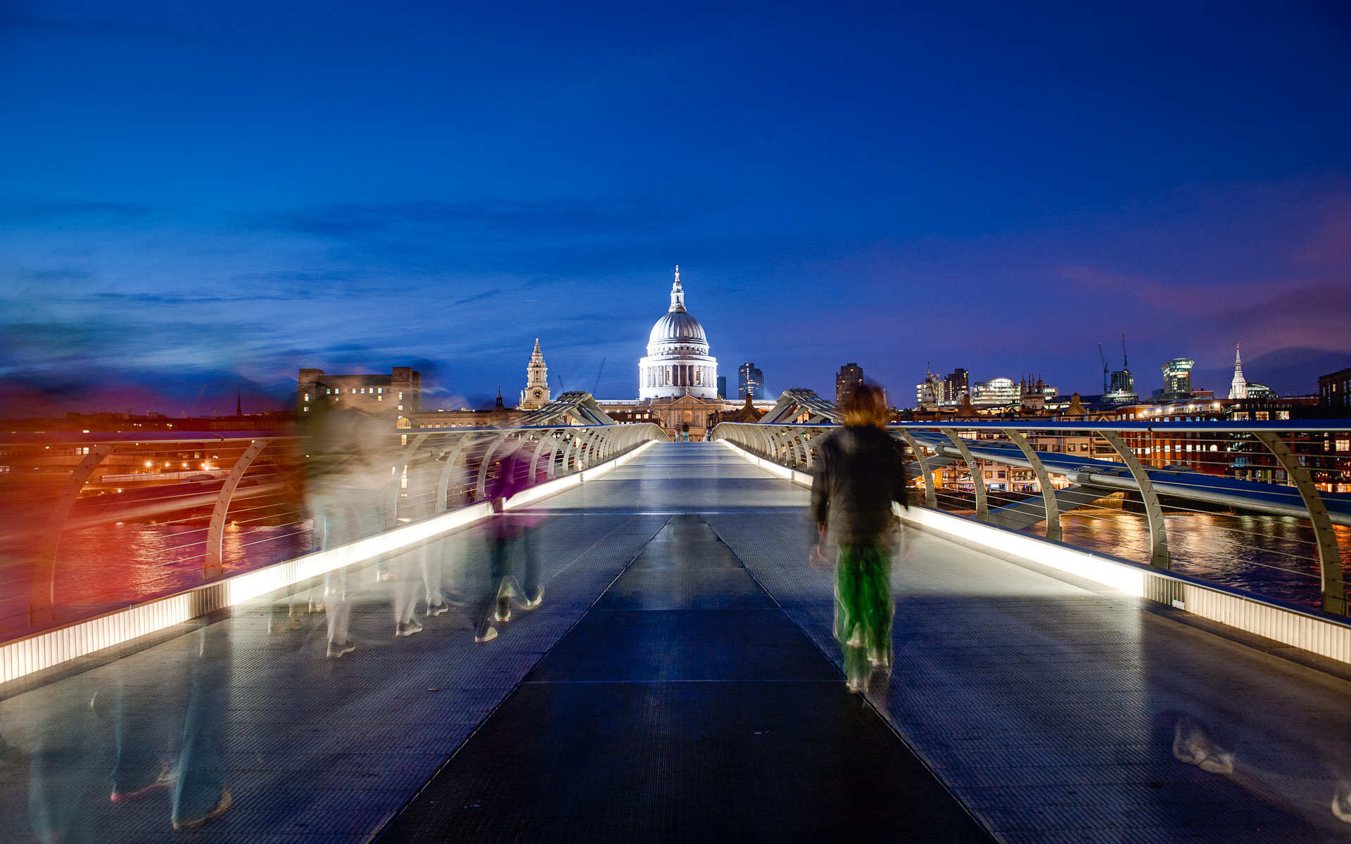 Low light night shot people walking across Millennium Bridge towards St Pauls Cathedral London England