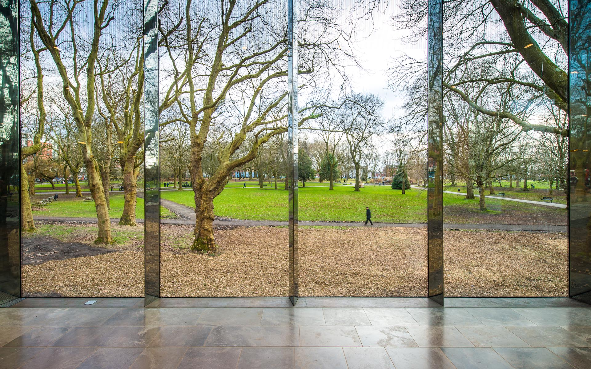 Interior daytime capture of Whitworth Art Gallery Manchester England glass panels view through to green park